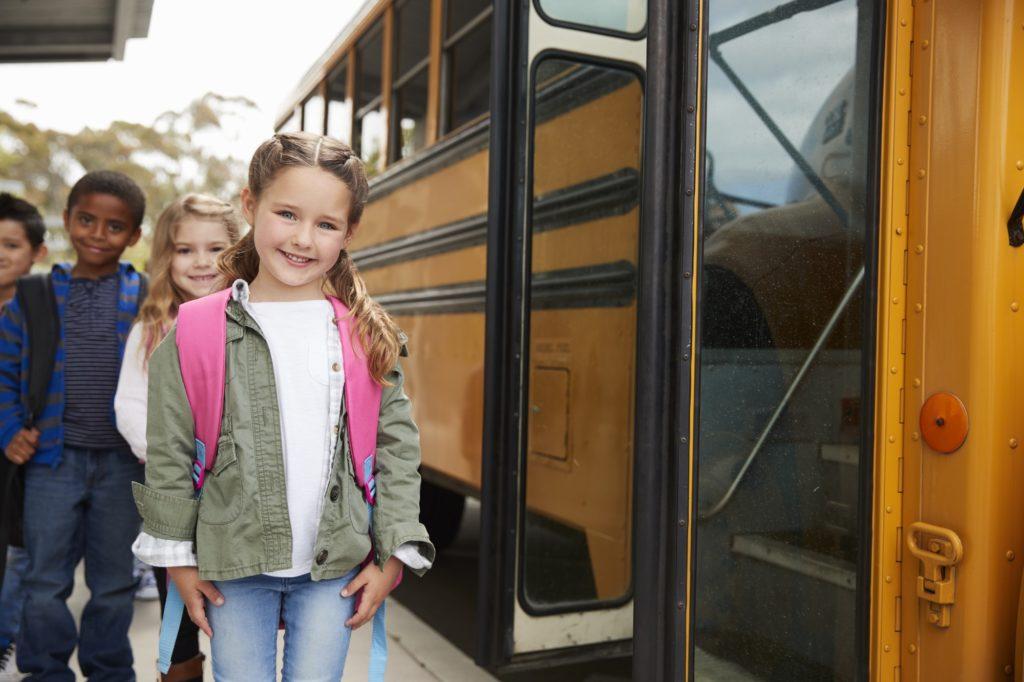 Elementary school kids waiting to board the school bus